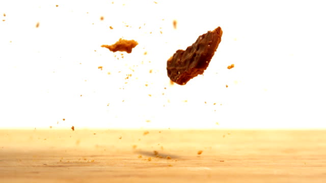 Biscuit falling and breaking on wooden table Biscuit falling and breaking on wooden table in slow motion cookie stock videos & royalty-free footage