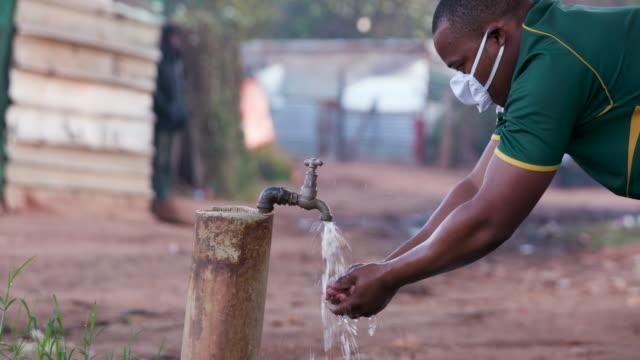 vídeos de stock, filmes e b-roll de homem negro africano lavando as mãos em uma torneira/torneira externa em um campo de posseiros para prevenir a infecção por covid-19 durante a pandemia coronavírus - higiene