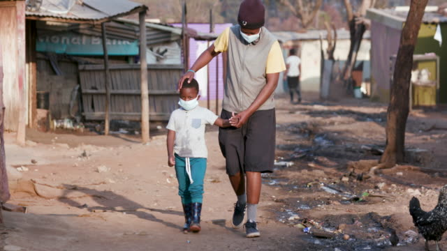 Black African mother and child walking in an informal settlement with protective face masks to prevent Covid-19