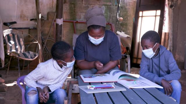 Black African woman home schooling her two young children at their dilapidated home during lockdown for Covid-19 Coronavirus pandemic, South Africa