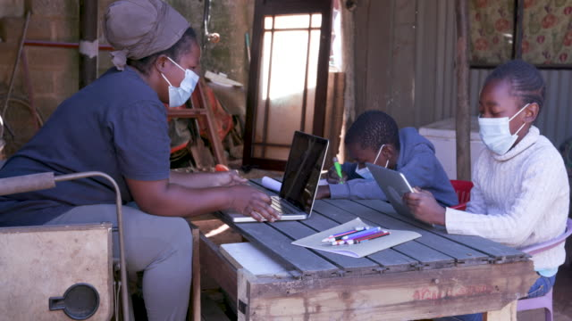black african woman using a laptop and digital tablet to home school her two young children at their dilapidated home during lockdown for covid-19 coronavirus pandemic, south africa - wieś filmów i materiałów b-roll