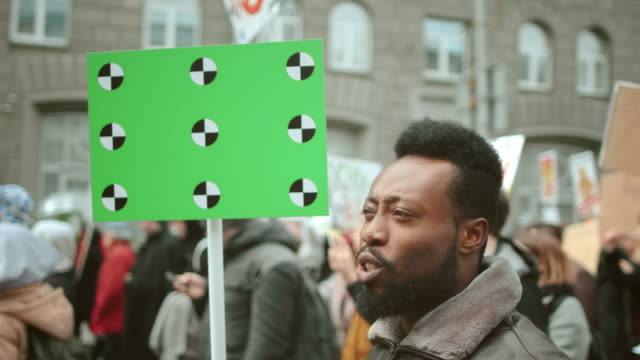 Black afro American man scream a political protest strike event. Crowd people. video