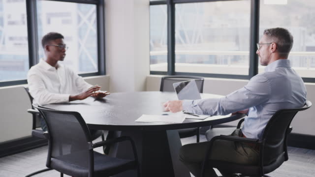 A black and a white businessman in a meeting room for a job interview, close up, selective focus