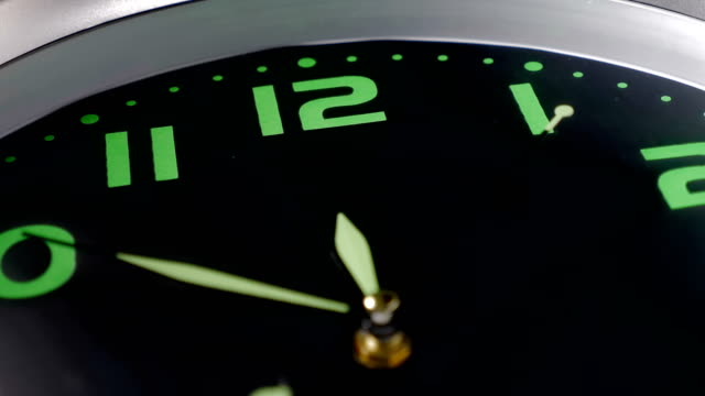black and green wall clock with the second hand moving - macro