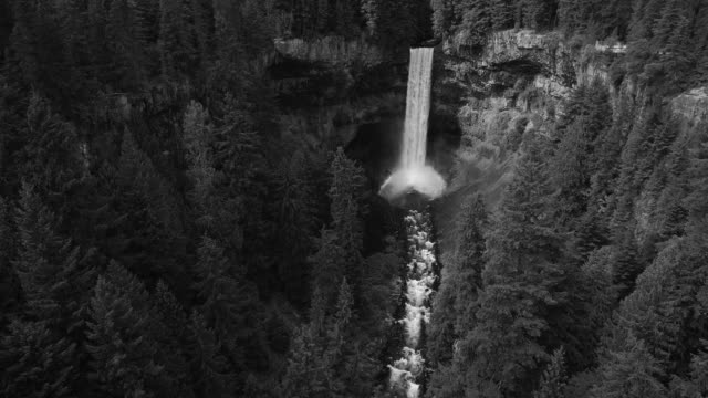 Black and White Aerial of Waterfall in Forest Canyon Flowing into Huge Crater video
