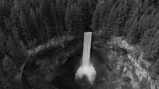 Black and White Aerial of Waterfall Slow Motion Flowing Over Canyon Cliff into Crater video