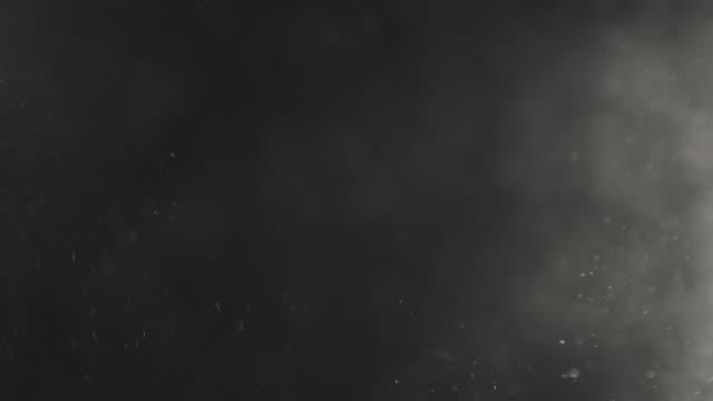 vídeos de stock, filmes e b-roll de explosão de partículas de poeira de preto e branco retroiluminado e flutuante em câmera lenta - poeira