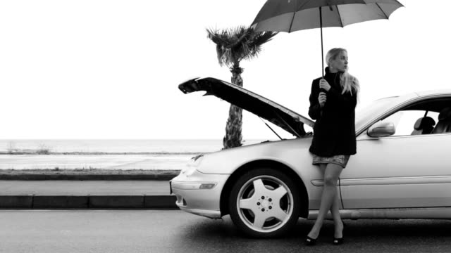 Black and white footage of a woman standing under the umbrella near the broken auto video