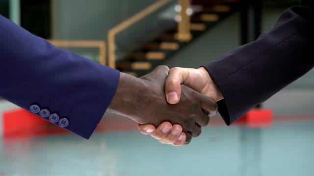 schwarz / weiß menschenhand mit business-bekleidung in einem modernen händedruck zu einander freundschaft und respekt zeigen. - hände schütteln stock-videos und b-roll-filmmaterial