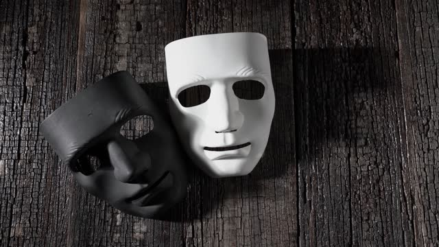 Black and white masks on a wooden vintage background, symbol of anonymity and theater. With shadows close-up, copy space