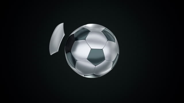 Black and white metallic football flying in and out on dark background. video