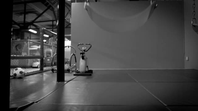 Black and white: recently-left indoor playground with a swing still swaying video