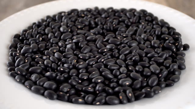 Black beans rotating on a white plate. Seamless loopable. Prores FullHD video