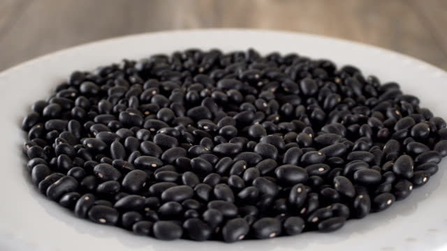 Black beans rotating on a white plate. Seamless loopable video