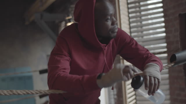 Black Boxer in Hoodie Leaning on Ropes and Drinking Water