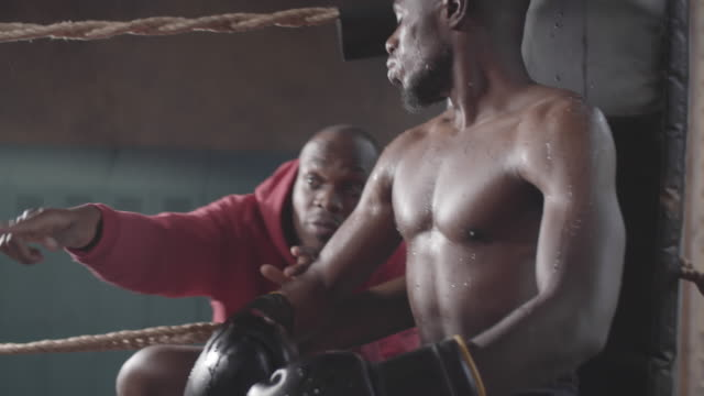 Black Boxer Listening to Agitated Coach in Ring Corner during Amateur Match