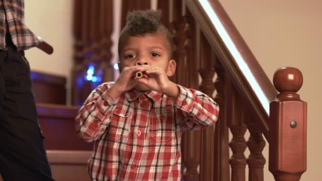 stockvideo's en b-roll-footage met zwarte jongen spelen fluit. - christmas tree