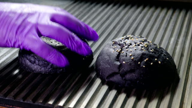 black bun. two halves of hamburger bread are being fried on grill for burger. 4k - sesamo video stock e b–roll