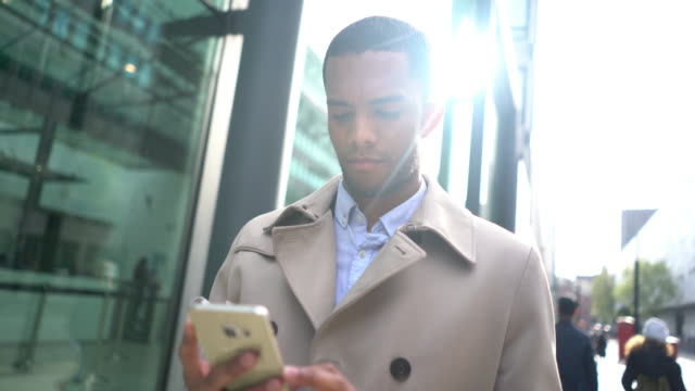 Black business man outdoors texting on his smartphone video