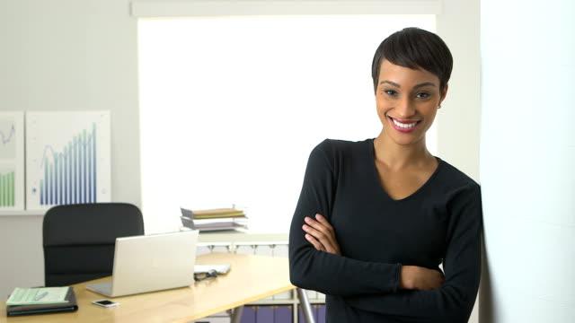 Black business woman standing in doorway smiling video
