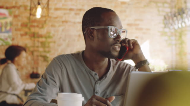 vídeos de stock e filmes b-roll de black businessman chatting on cell phone in cafe - remote work