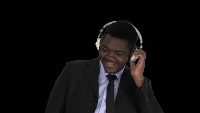Black businessman dancing to music in headphones, Alpha Channel
