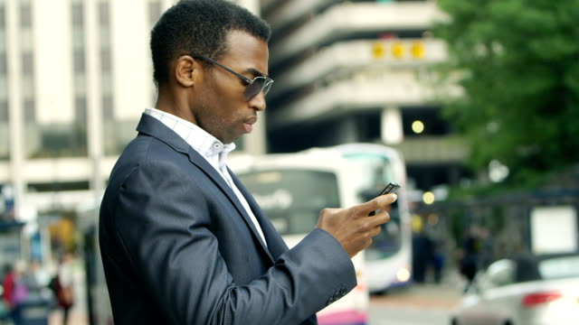 black businessman using cell phone with city urban background video