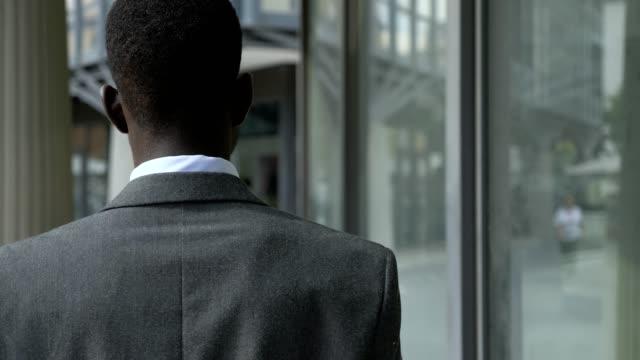 schwarze geschäftsmann herein innenverteidiger blick auf die straße, stadt - hinter stock-videos und b-roll-filmmaterial