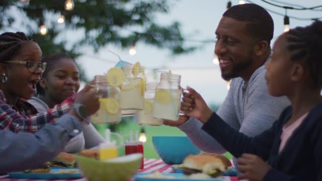 vídeos de stock e filmes b-roll de black canadian family cheersing with lemonade glasses - limonada tradicional