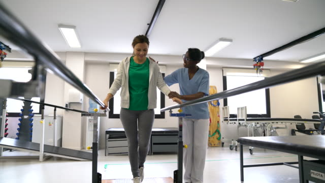 black cheerful therapist motivating female patient walk with the help of parallel bars - fisioterapia video stock e b–roll