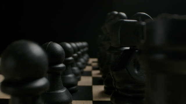 black chess pieces in start row position ready to game concept - mata filmów i materiałów b-roll