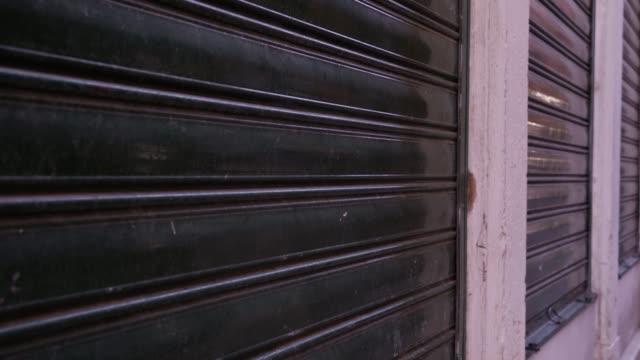 vídeos de stock, filmes e b-roll de persianas pretas fechadas em janelas de loja na rua da cidade - característica arquitetônica