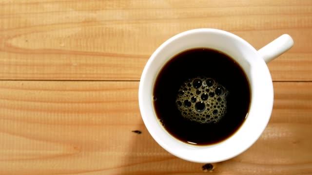 schwarzer kaffee in eine weiße tasse auf holztisch und hand aufheben - kaffeetasse stock-videos und b-roll-filmmaterial