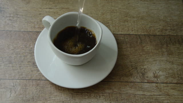 black coffee mixing by hot water pouring black coffee mixing by hot water pouring on glass boiled stock videos & royalty-free footage