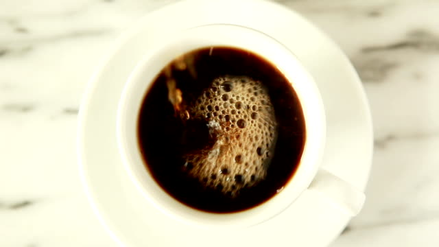 Black Coffee Pour Closeup view from above of coffee being poured into white coffee cup on marble table pouring stock videos & royalty-free footage