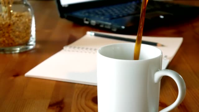 Black coffee pouring from bottle into a cup on wooden table with office supplies on background Black coffee pouring from bottle into a cup with office supplies on background coffee break stock videos & royalty-free footage