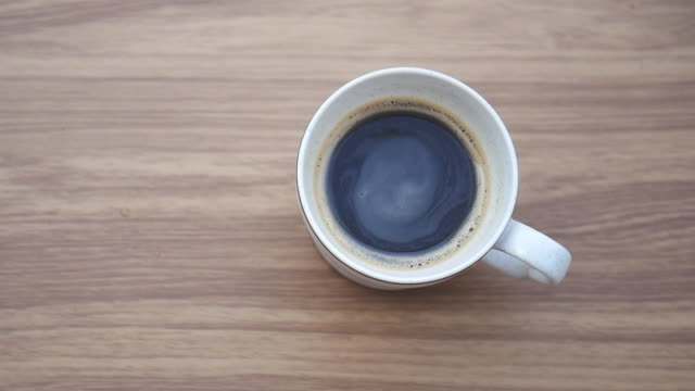 Black coffee with brown sugar.Stirring coffee with spoon.
