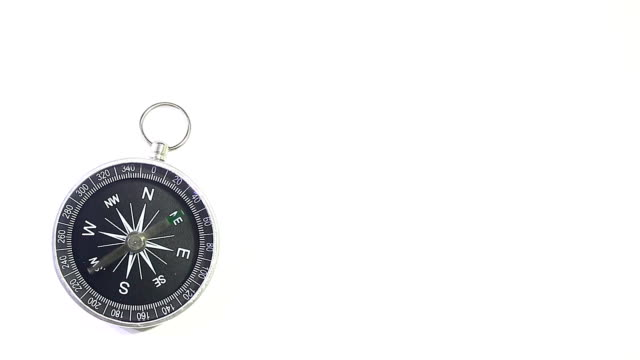 Black Compass on White Background A silver and black compass pointing north on a white background. navigational compass stock videos & royalty-free footage