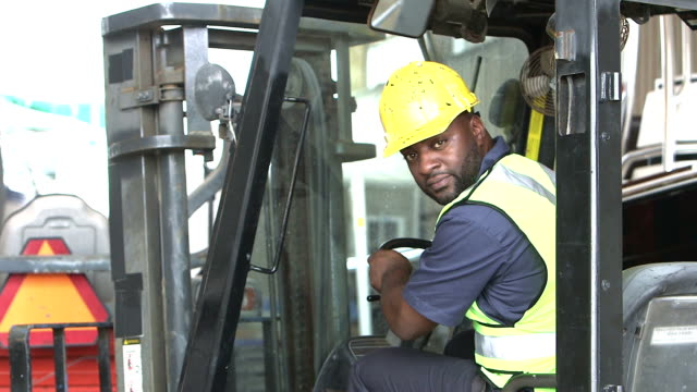 Black construction worker climbing onto forklift A black man in his 30s working in the construction industry. He is wearing a hardhat and safety vest. He walks up to a forklift, climbs into the driver's seat, and looks over his shoulder at the camera. forklift stock videos & royalty-free footage