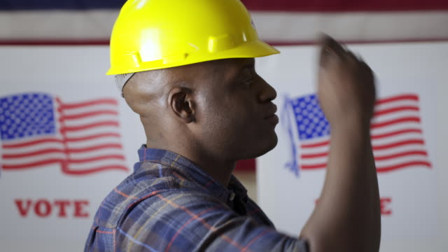 Black contractor puts on hard hat with