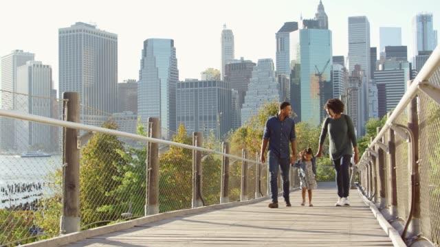 흑인 부부와 딸 맨하탄에 인 도교에 산책 - 방관적인 사람들 스톡 비디오 및 b-롤 화면