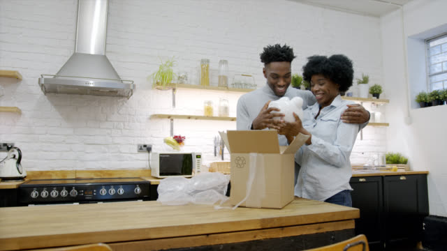 Black couple at home unpacking their piggybank with their savings and looking very happy