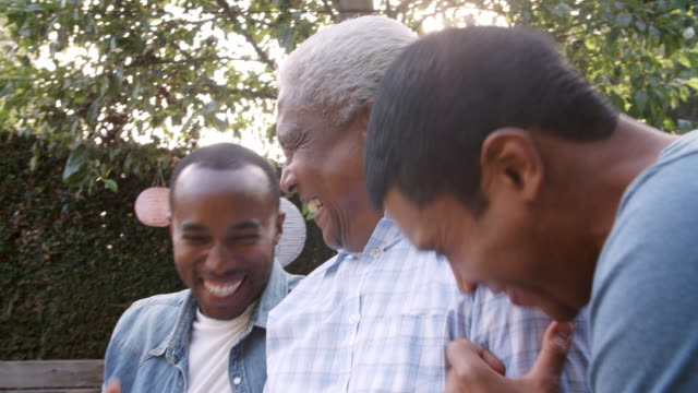 Black dad and two adult sons laughing together in garden