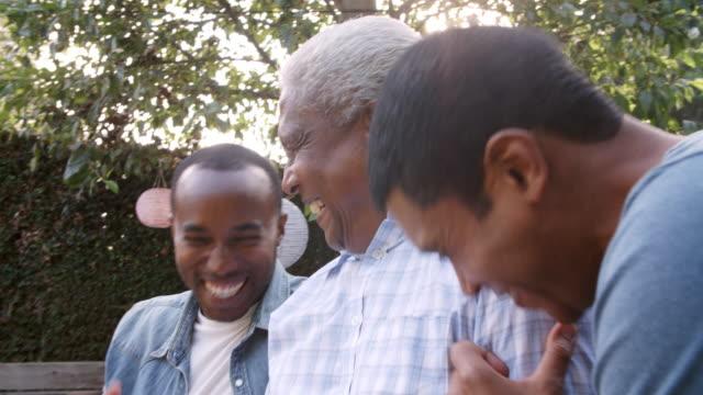 Papá negro y sus dos hijos adultos riendo juntos en el jardín - vídeo