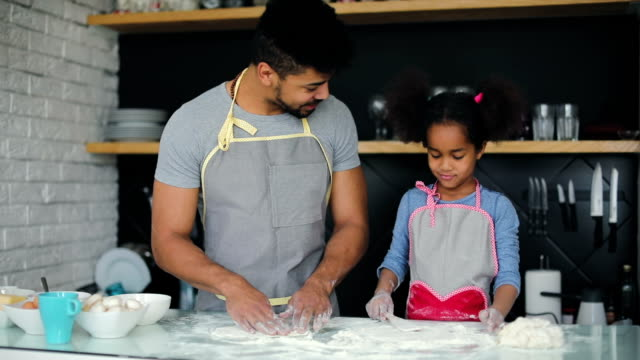 Black dad and young daughter making pizza video