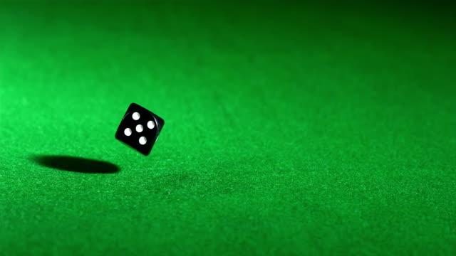 Black dice falling on green table and spinning video