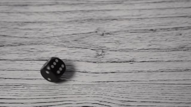 black dice rolls and spins on a white textured wooden old table - fianco a fianco video stock e b–roll