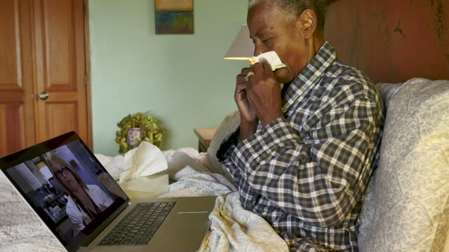 Black elderly woman with a respiratory illness video chatting with her doctor
