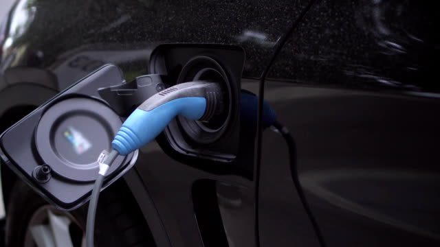 Black electric car with rechargeable batteries at charging station. Close up of hybrid vehicle video