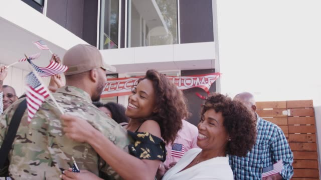 vídeos de stock e filmes b-roll de black family running out of their house to greet a soldier returning home - regresso ao lar
